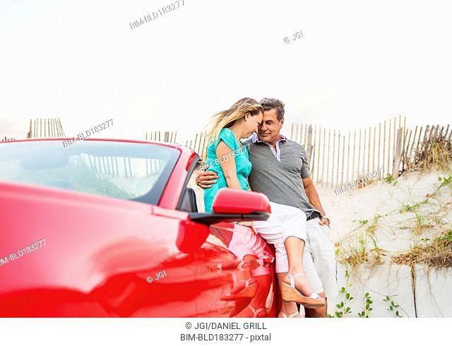 Caucasian couple sitting on convertible