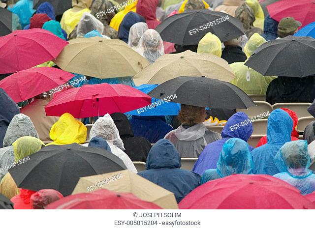 Guests hold umbrellas in the rain during the official opening ceremony of the Clinton Presidential Library November 18, 2004 in Little Rock, AK
