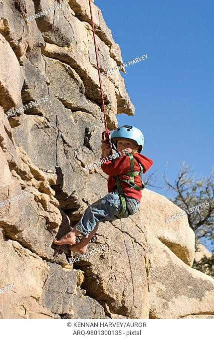 Boy rappelling cliff face, Joshua Tree National Park, California