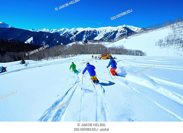 Rear view of men skiing down snow covered ski slope, Aspen, Colorado, USA