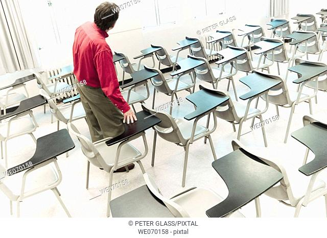 Man standing among student desks in an empty college classroom