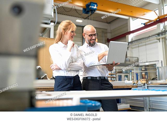 Smiling businessman and businesswoman using laptop in factory