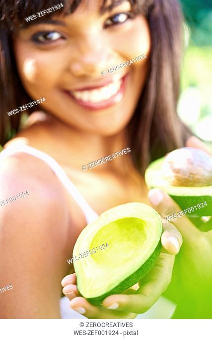Woman offering half of avocado