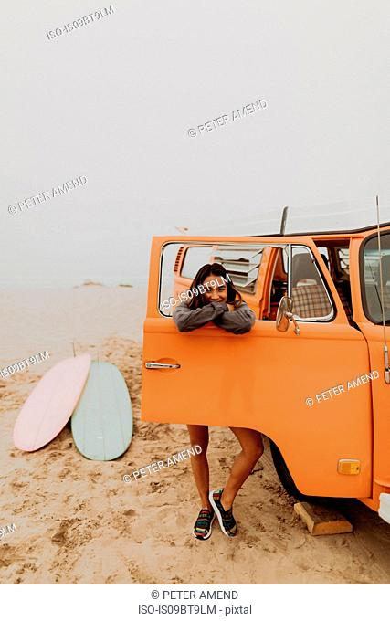 Young woman leaning on recreational vehicle window at beach, portrait, Jalama, California, USA