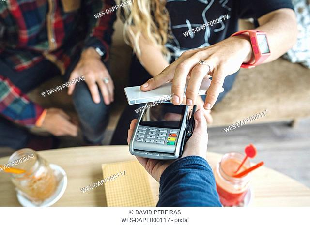 Woman paying with smart phone in cafe