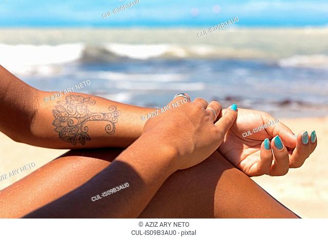 Cropped view of tattooed woman on beach