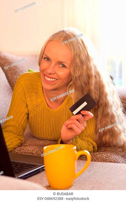 Happy young woman lying on sofa in front of laptop and showing credit card. Online shopping concept
