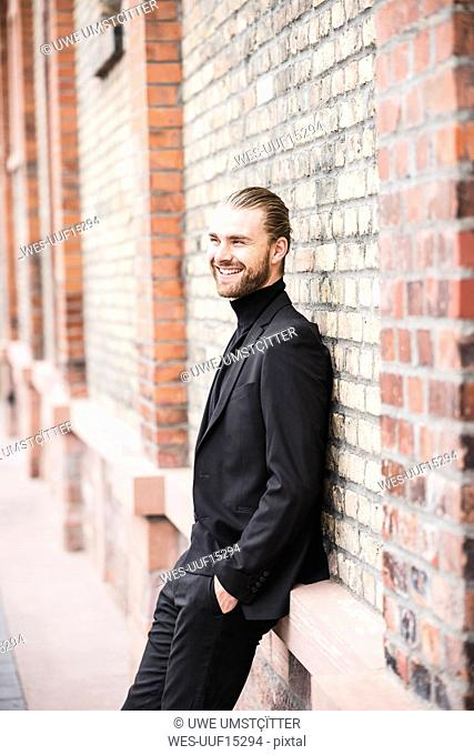 Smiling fashionable young man leaning against brick wall