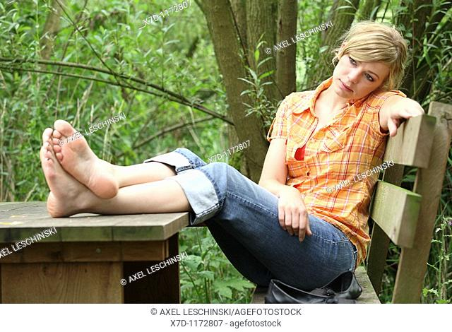 blond woman sitting on bench resting with legs on table