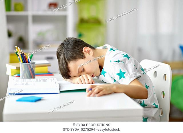 tired student boy sleeping on table at home
