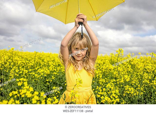 Portrait of blond little girl with yellow umbrella wearing yellow dress standing in rape field