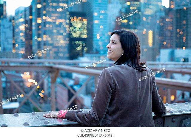 Female tourist looking out from Brooklyn Bridge, New York, USA