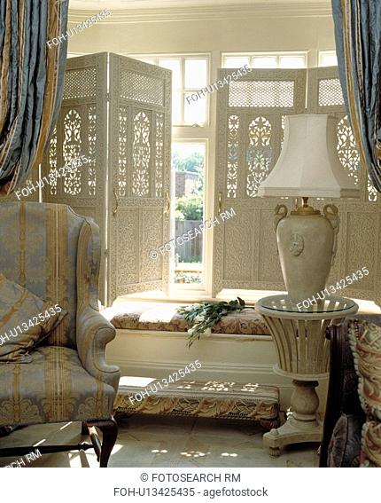 White fretwork shutters on window in traditional living room
