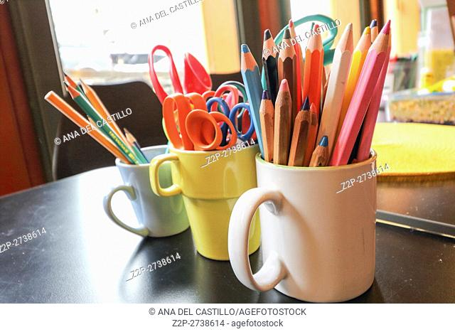 Assortment of scissors and Colored drawing pencils in a variety of colors on desk