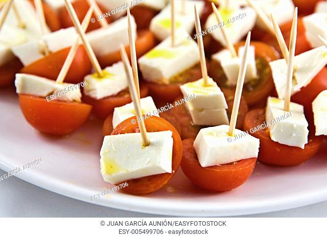 Cherry tomato brochettes with cottage cheese and drops of olive oil