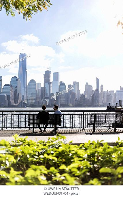 USA, two businessmen sitting on bench at New Jersey waterfront with view to Manhattan