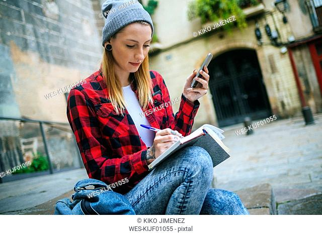 Spain, Barcelona, young woman with cell phone sitting on stairs writing in notebook