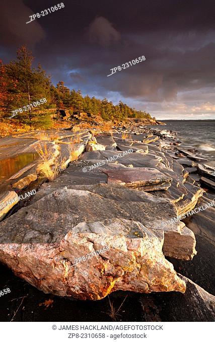 Dark clouds over Georgian Bay and a rocky shoreline. Parry Sound, Ontario, Canada