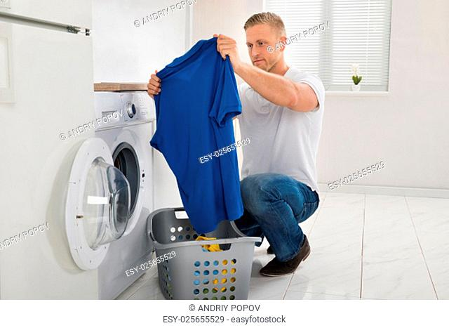 Young Man Looking At T-shirt While Using Washing Machine Appliance In Kitchen