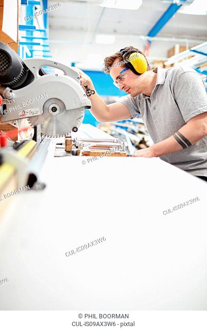 Male factory worker using circular saw in roller blind factory