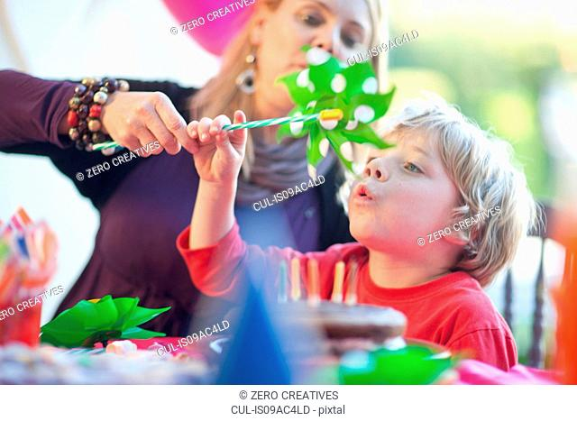 Young boy blowing windmill at birthday party