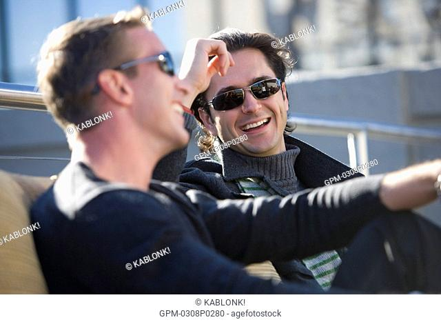 Portrait of young men relaxing and laughing on rooftop of downtown condo