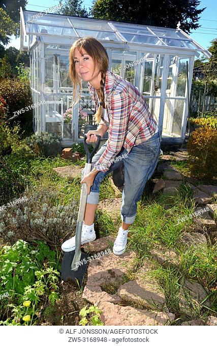 Woman, 40 yeras old, digging in her garden in Ystad, Scania, Sweden