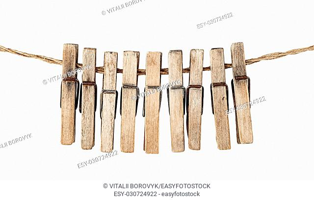Many old wooden clothespins on a rope isolated on white background