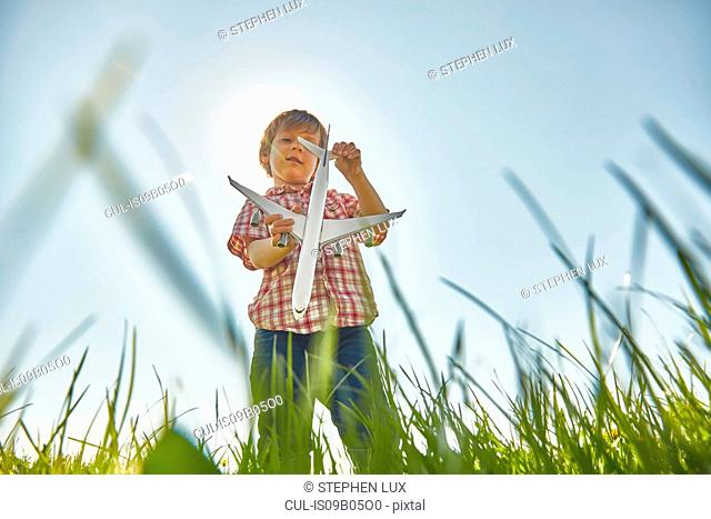 Low angle view of boy standing in grass checking toy airplane tail