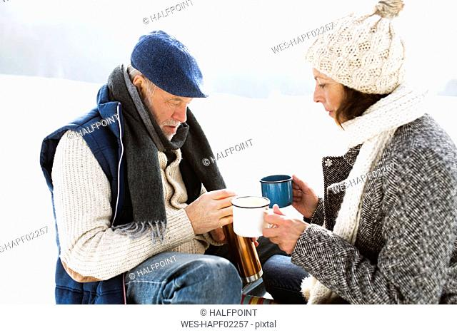 Senior couple having a break with hot beverages in snow