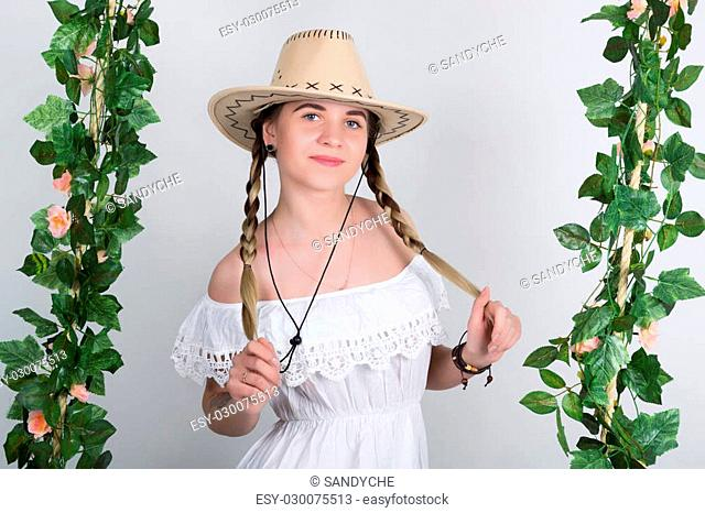 Beautiful young leggy blonde in a little white dress and white cowboy hat on a swing, wooden swing suspended from a rope hemp, rope wrapped vine and ivy