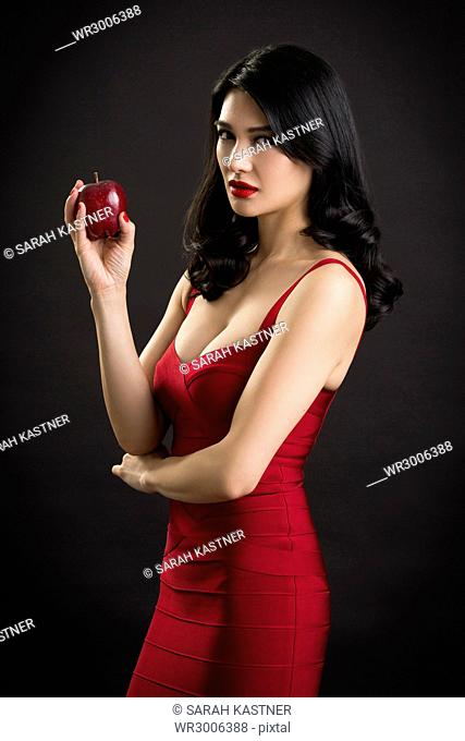 Woman in red evening dress with apple