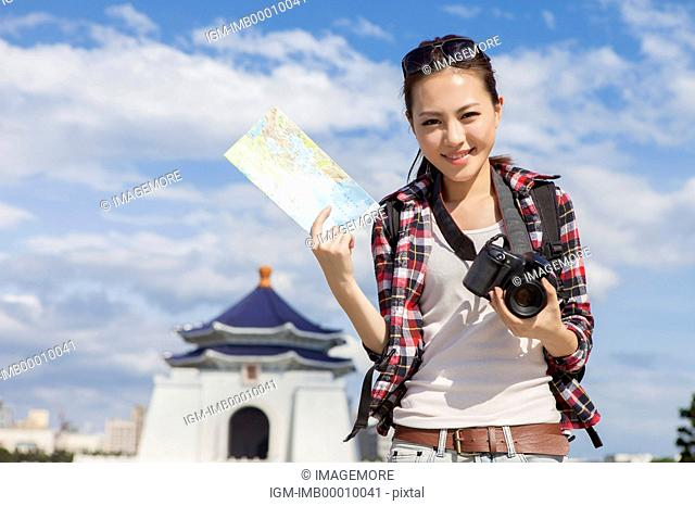 Young woman holding camera and map with smile