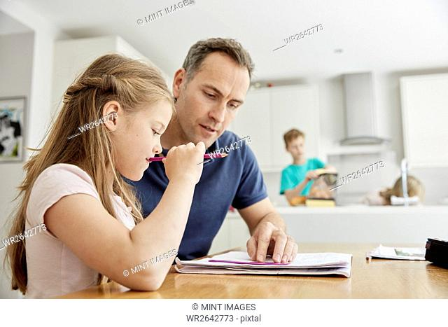 A young girl and her father sitting looking at her school books, doing her homework