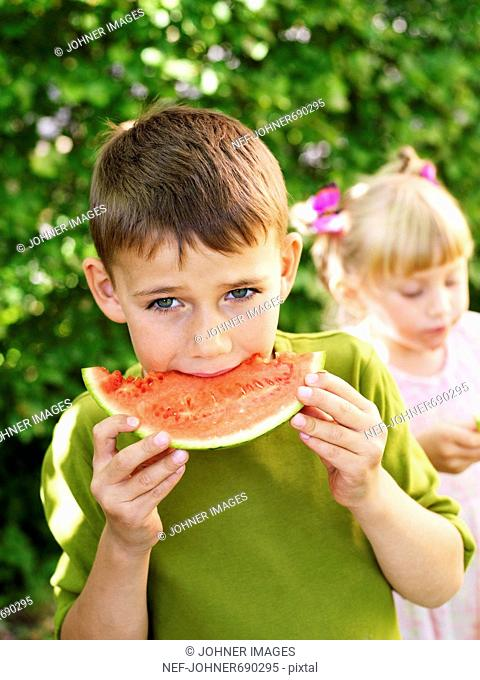 Boy and girl eating watermelon, Sweden