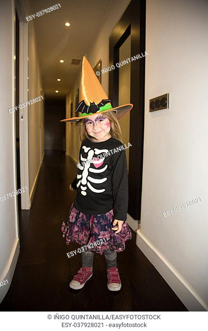 portrait of four years old blonde little girl in disguise for Halloween, with orange witch hat, black sweater with white skeleton and painted face