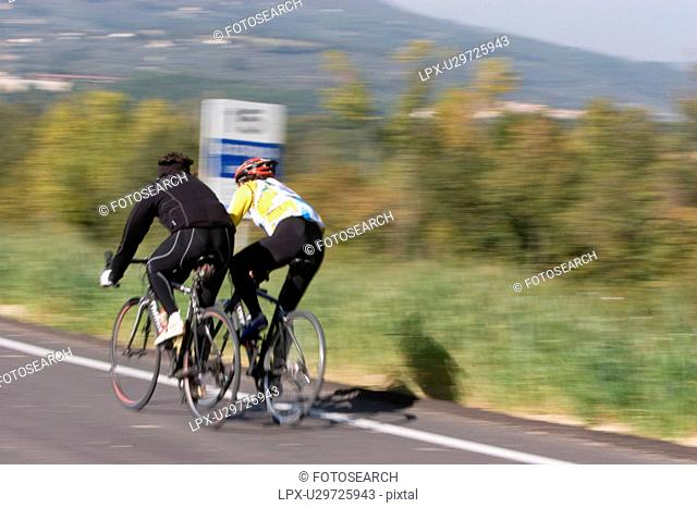 Rear view of 2 cyclists in training gear, cycling along road in morning autumn sun, Umbria, Italy, with green fields and trees in background