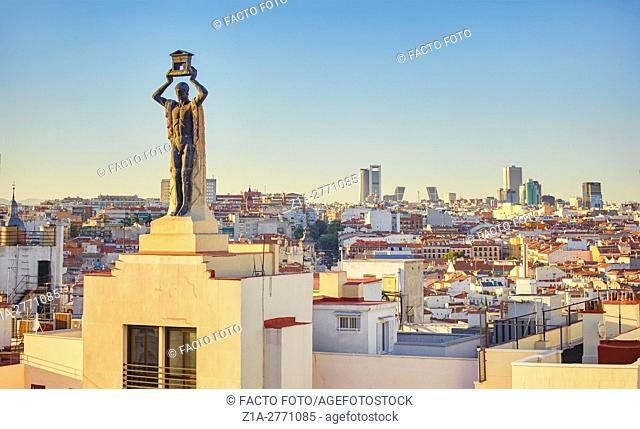 ÒThe RomanÓ sculpture (1930), by Victorio Macho, located at the top of 60 Gran Via Street building and Madrid skyline. Madrid. Spain