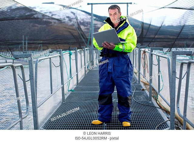Worker using laptop at salmon farm