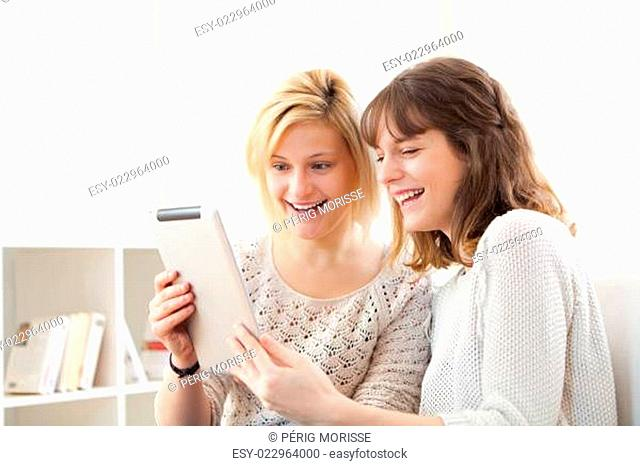 Girls laughing and watching funny things on tablet
