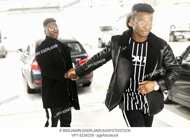 man walking away from friend, holding hands, in car parking garage, leaving, in Munich, Germany