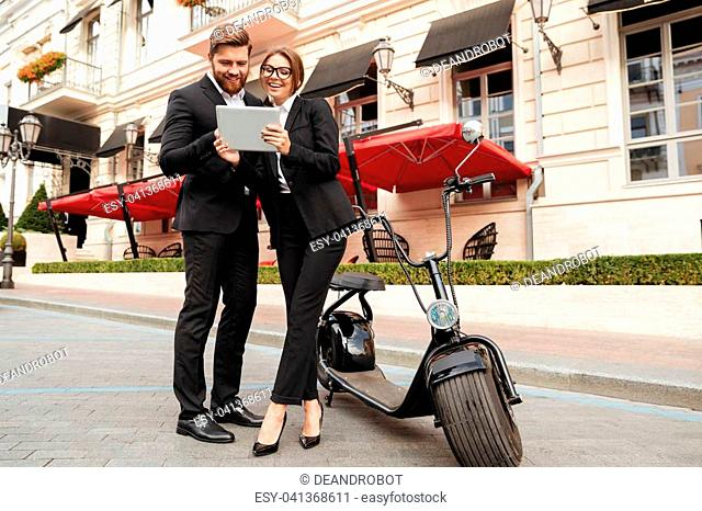 Full length portrait of a beautiful young couple in smart clothes standing and using tablet computer on a city street near motorbike