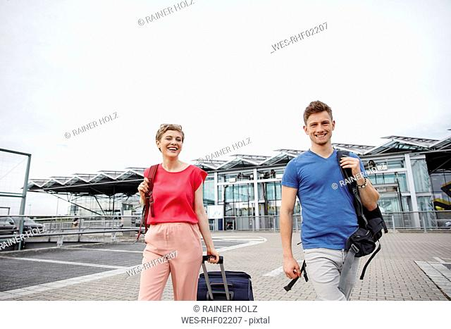 Happy couple walking outside airport