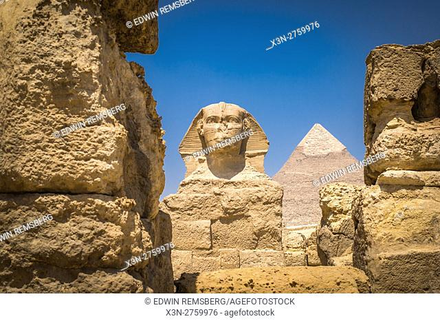 Cairo, Egypt the Great Sphinx of Giza standing tall with the Great Pyramids of Giza in the background. This particular one is The Pyramid of Khafre