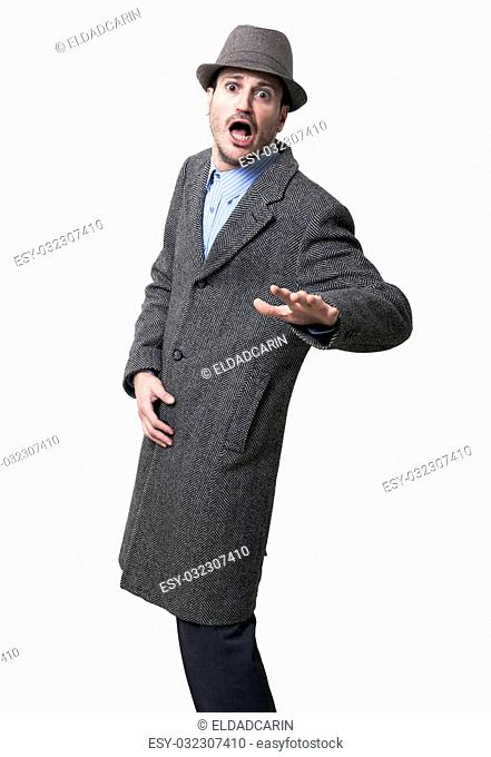 A young adult dressed in a gray overcoat and a gray hat, frozen in the middle of turning towards the camera with a surprised and fearful expression on his...