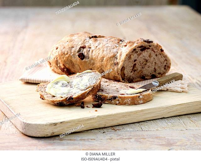 Sliced fruit and nut sourdough bread smeared with butter and butter knife