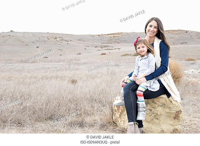 Portrait of mother and daughter sitting on rock