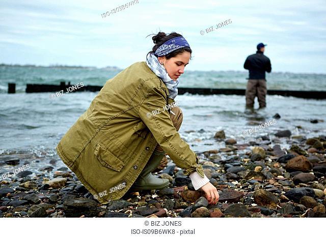 Young woman crouching on beach while boyfriend sea fishing