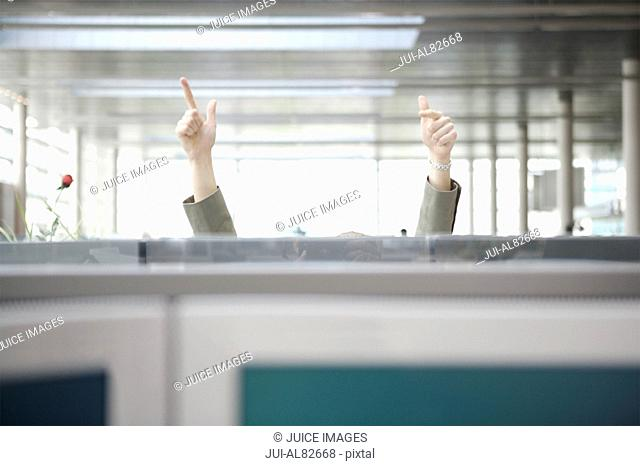 Businessman with hands in air behind cubicle wall
