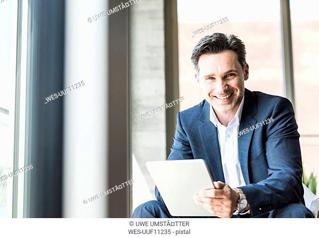 Portrait of smiling businessman with tablet
